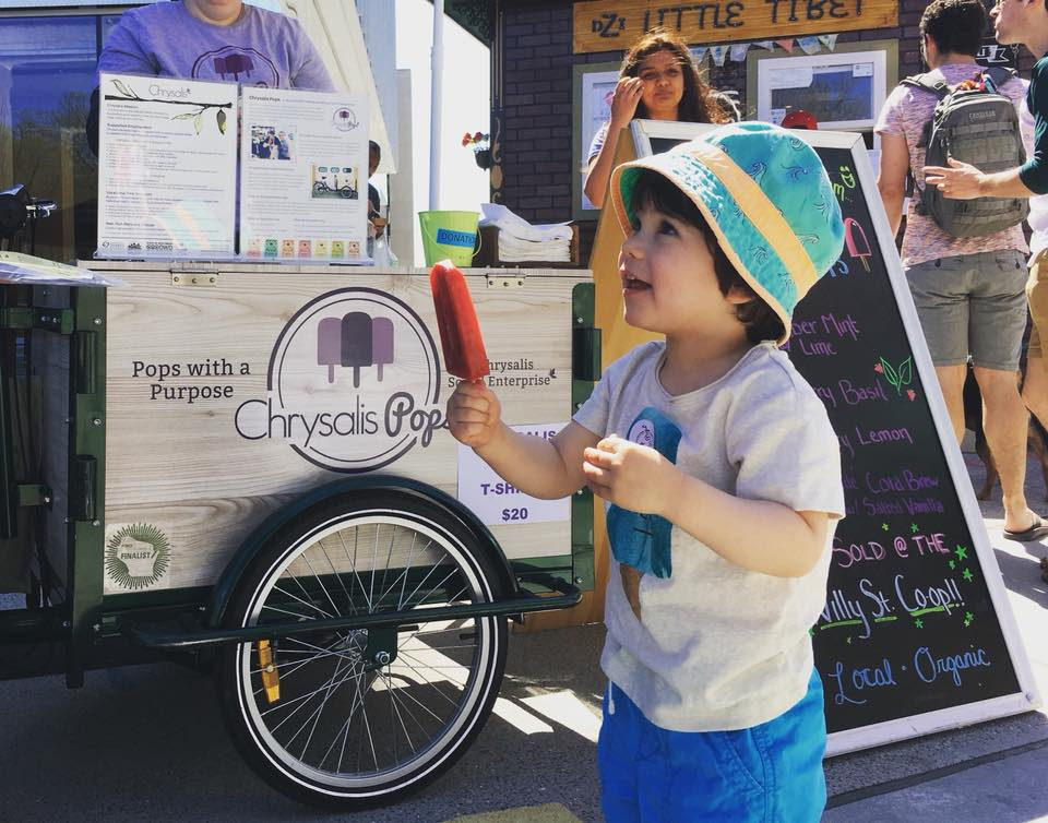 child holding popsicle in front of chrysalis cart