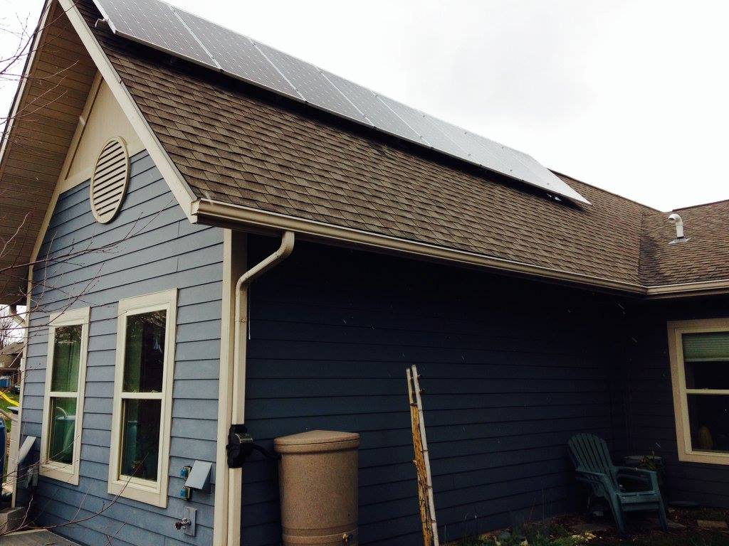 blue house with installed solar panels from madison area community land trust