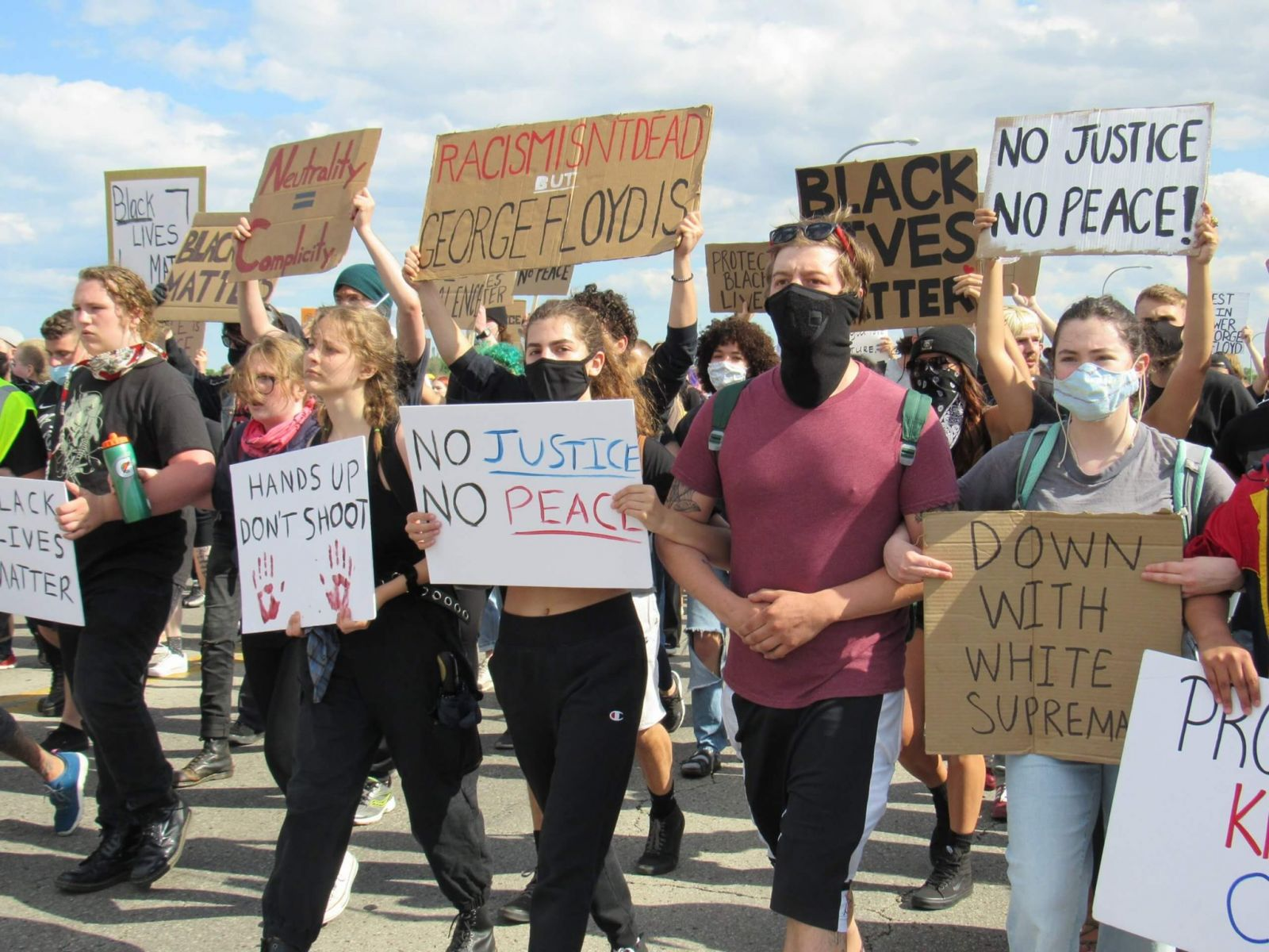 young people at a rally shared on progressive facebook account holding signs for BLM movement